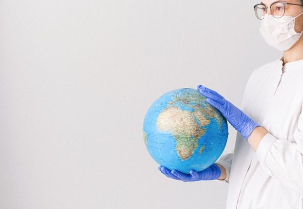 person-with-a-face-mask-and-latex-gloves-holding-a-globe-4167539
