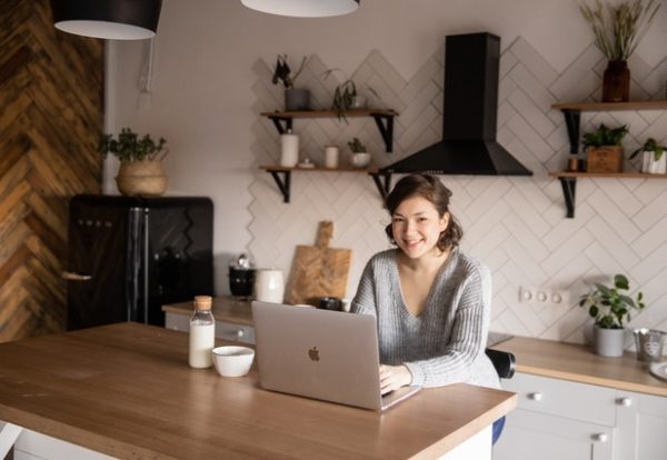 young-woman-using-laptop-in-kitchen-4049786